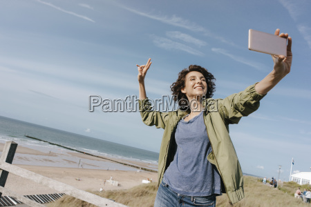 happy woman at the beach taking