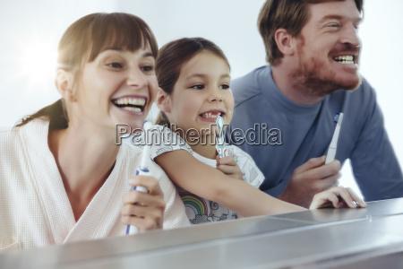 dreikoepfige familie putzt sich die zaehne