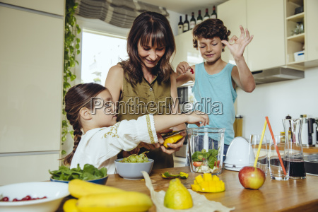 mother and children putting fruit into