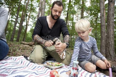 man cutting bread during a picnic