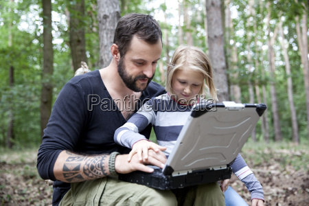 father and daughter in forest using