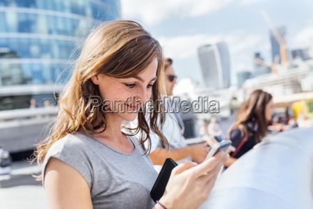 uk london smiling woman checking her