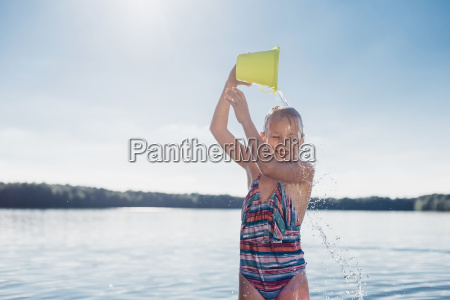 portrait of smiling girl pouring water