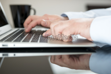 man sitting at desk working with