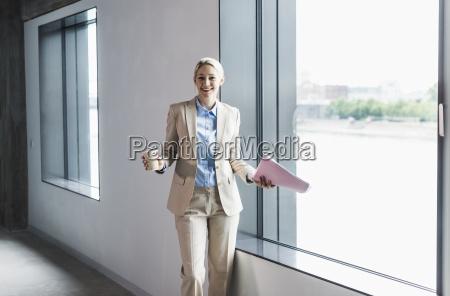 portraet der laechelnden geschaeftsfrau mit kaffee