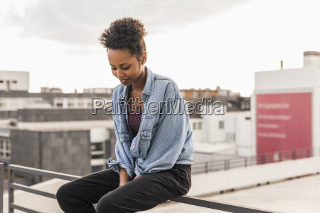 young woman sitting on railing on