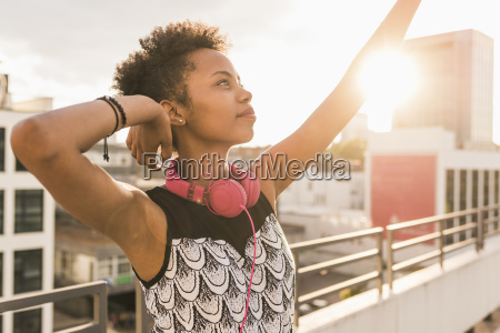 young woman with headphones on rooftop