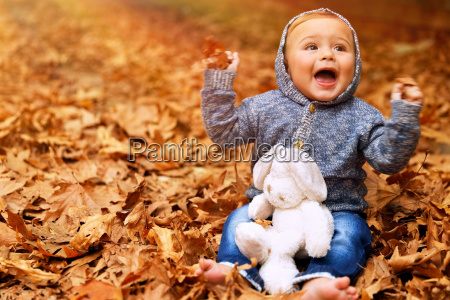 baby boy playing in autumn park