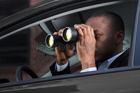 afrikanischer mann der durch fernglas schaut