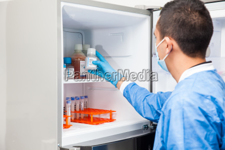 young male scientist and laboratory freezer