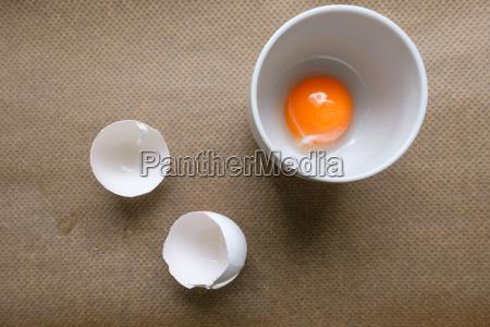 eigelb in tasse und weisse eierschalen