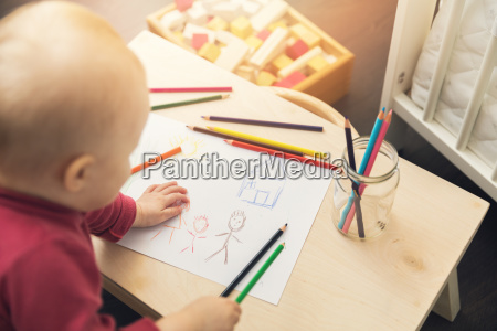 child drawing family picture with colored