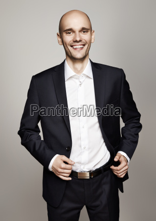 smiling man in black suit