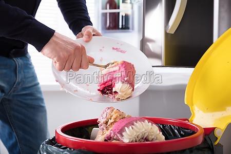 person wirft kuchen in papierkorb