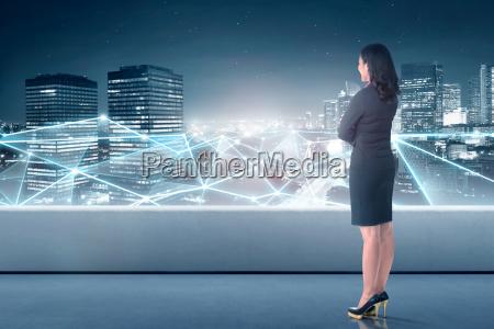 schoene asiatische geschaeftsfrau die netzwerkverbindung betrachtet
