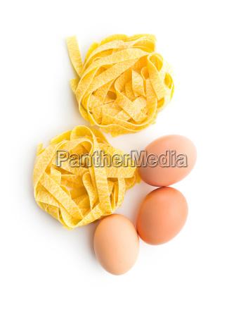 raw tagliatelle pasta und drei eier