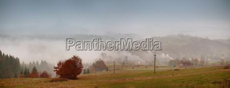 herbstnebel im bergdorf bewoelkter nebel
