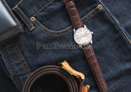 armbanduhr und geldbeutel auf jeansjeanstasche