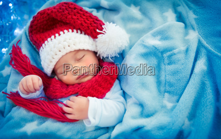 cute baby boy sleeping in santa