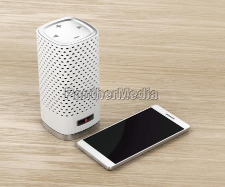 lautsprecher und smartphone auf hoelzernem hintergrund