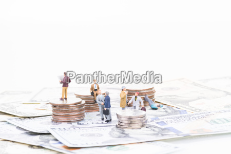 miniature business people on coins and
