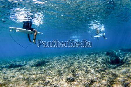 underwater view of surfers above reef