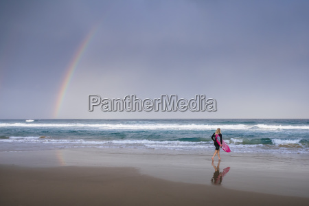 surfer walking on beach with rainbow
