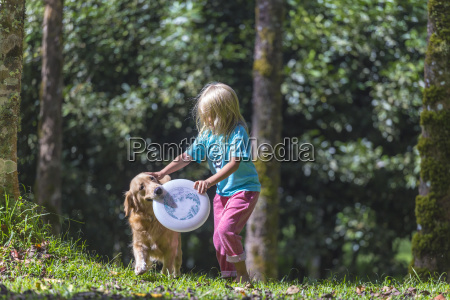 little girl playing frisbee with her