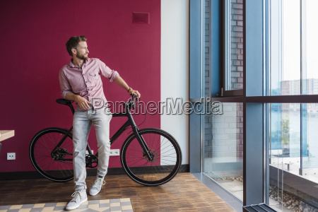 man with bicycle standing in modern