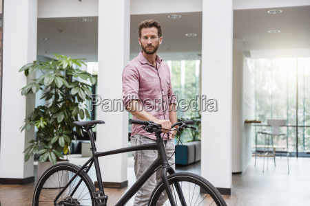 portrait of man with bicycle in
