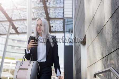 young businesswoman checking cell phone in