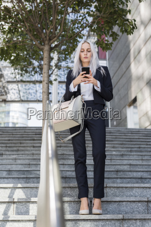 young businesswoman checking cell phone on