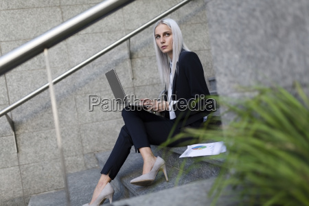 young businesswoman sitting on stairs in
