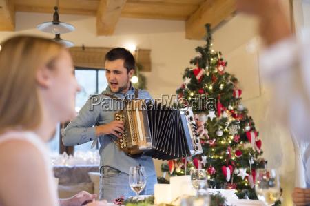 junger mann spielt akkordeon am weihnachtstisch