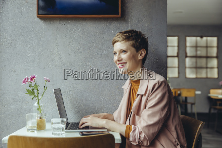 woman working in cafe with her