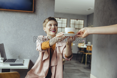 woman in cafe with laptop receiving