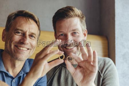 glueckliches schwules paar haelt ihre hochzeitsringe