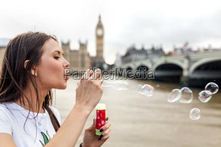 uk london woman making soap bubbles