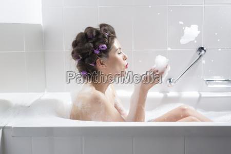 junge frau mit curlerndie ein bad