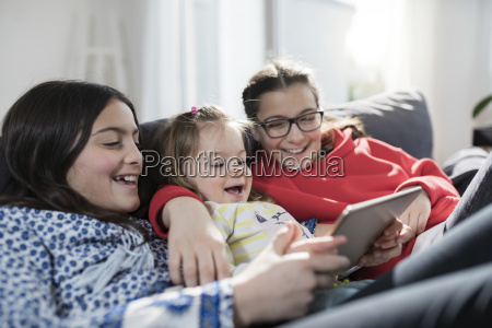 three sisters smiling and holding tablet