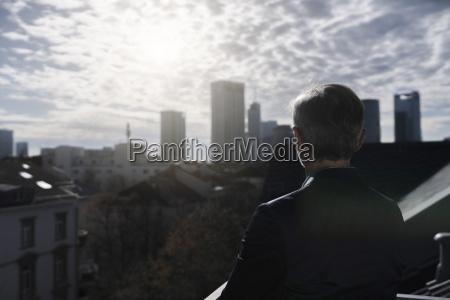 grauhaariger geschaeftsmann auf balkon mit blick