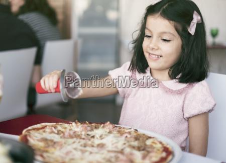 kleines maedchen mit ueberdimensionaler pizza in