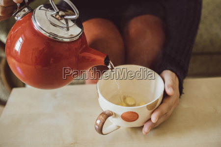 frau giesst wasser in teetasse mit