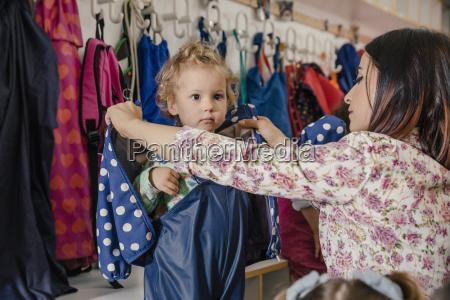 vorschullehrerin hilft maedchen beim anziehen von