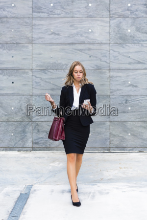 businesswoman with fashionable leatherbag looking at