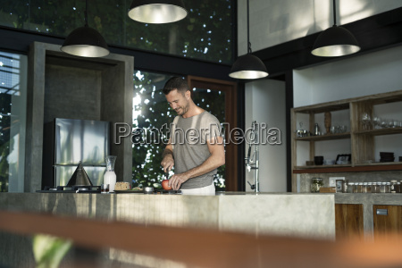 mature man standing in kitchen preparing