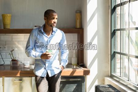 jungunternehmer steht in firmenkueche trinkt kaffee
