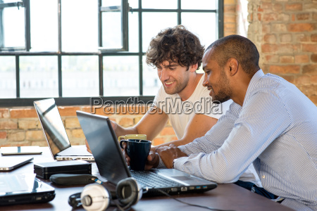 two young businessmen working together in