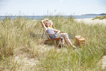 happy young woman sitting on beach