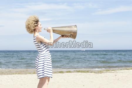 junge frau mit megafon am strand